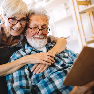 Beautiful old couple is reading a book and smiling while sitting at home