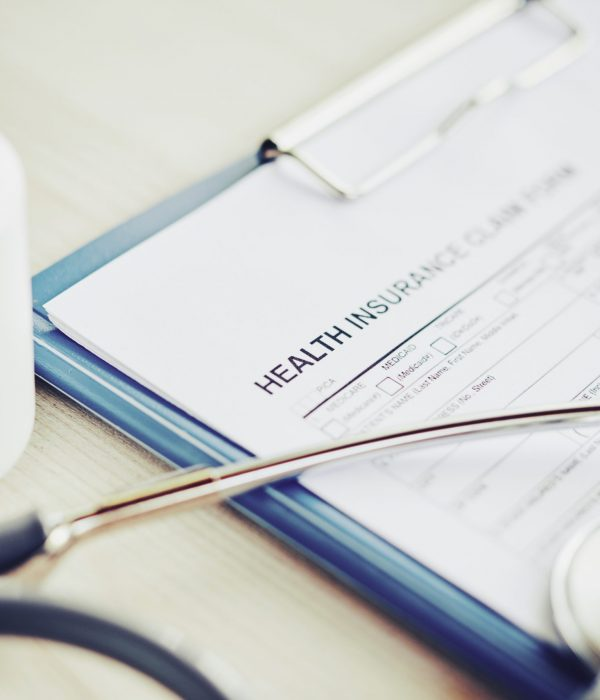 Close-up image of health insurance document, stethoscope and pills